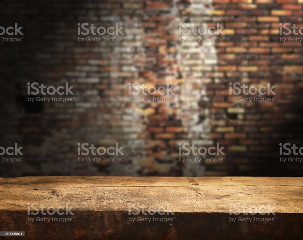 Rustic empty wooden table in front of brick wall stock photo