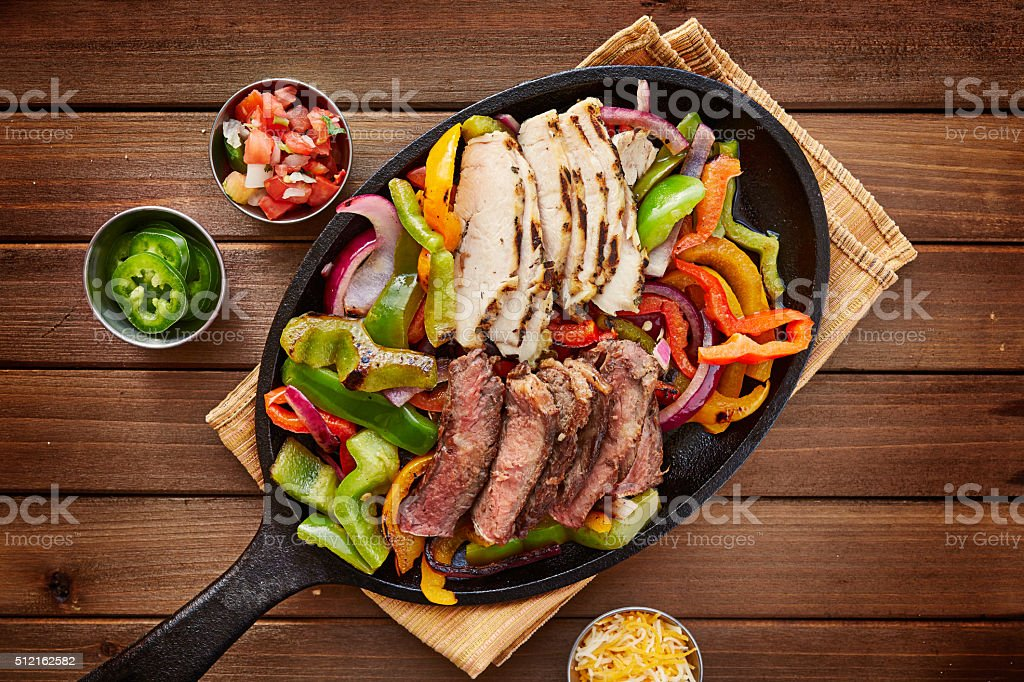 rustic fajita skillet meal with steak and chicken stock photo