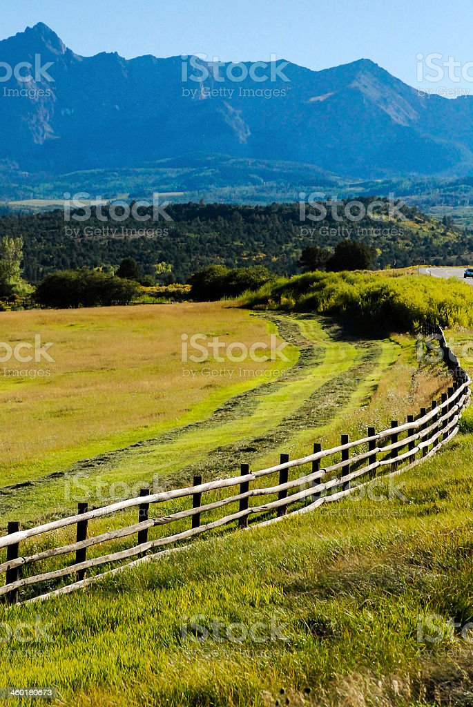 Rustic Fence Line and Cutting Hay San Juan Mountains Colorado stock photo