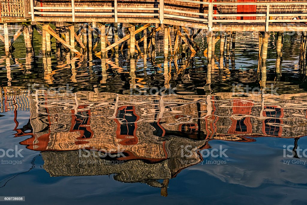 Rustic fishing shack in Maine reflected in water stock photo