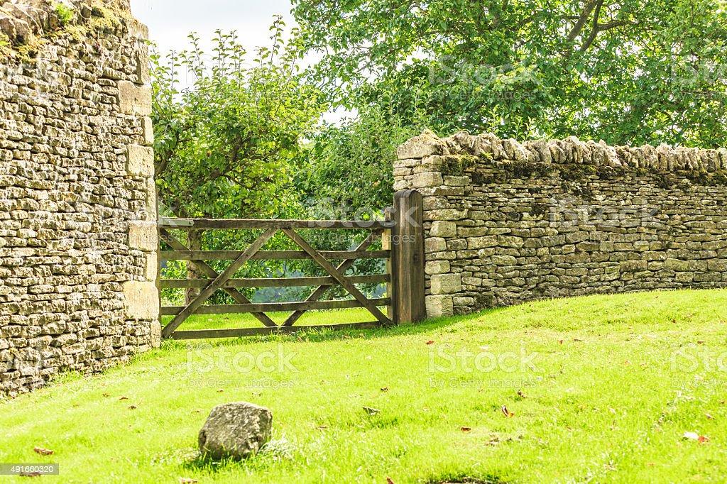 Rustic gate in drystone wall in Bibury England UK. stock photo