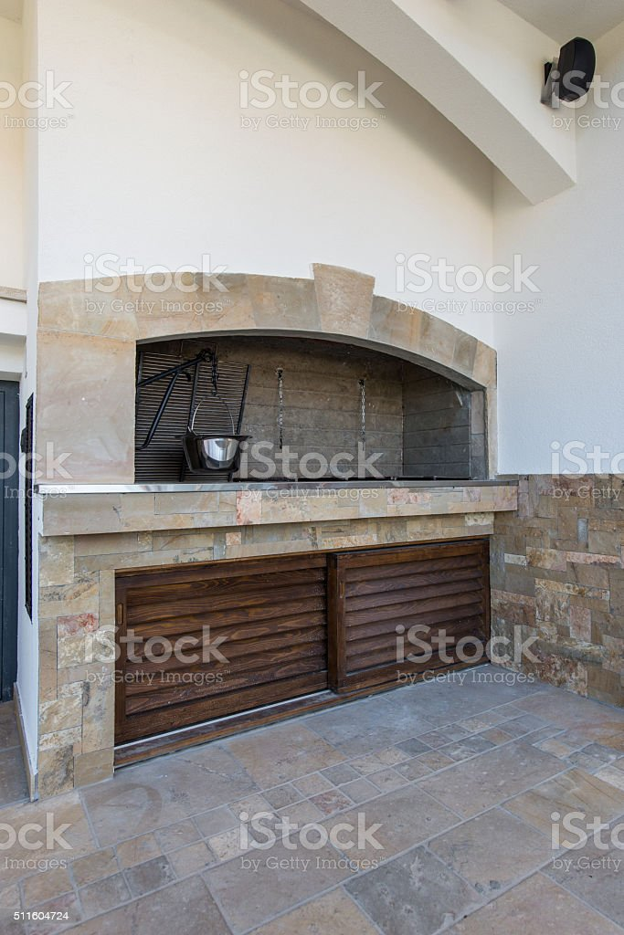 Rustic grill in outdoor kitchen in luxury villa exterior