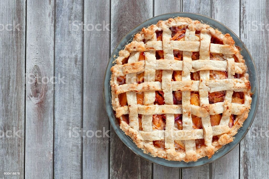 Rustic homemade peach pie, above view on wood stock photo