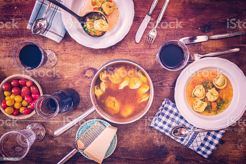 Rustic Homemade Tortellini Soup with Peas, Carrots, and Spinach Filling stock photo