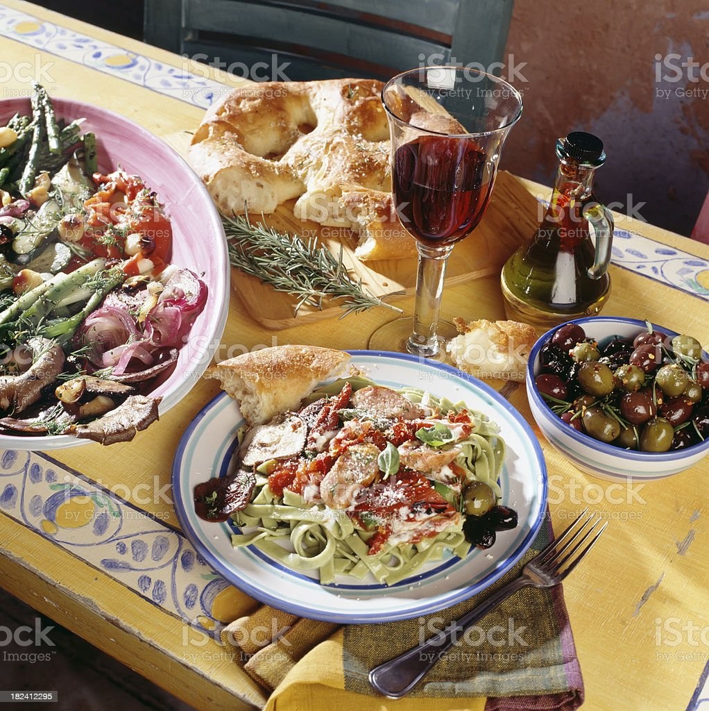 Rustic Italian Dinner with red wine olives and salad. royalty-free stock photo