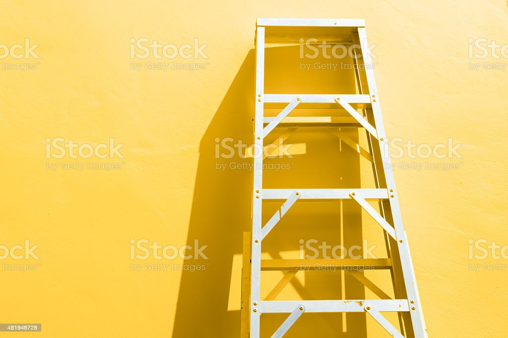 Rustic ladder leaning against a wall in the sunlight stock photo