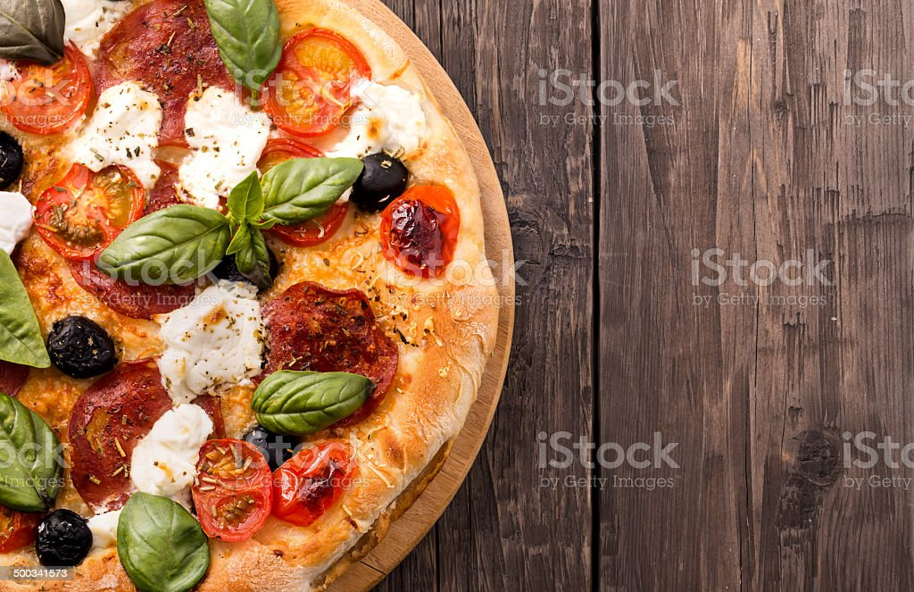 Rustic pizza with salami, mozzarella, olives and basil on wooden stock photo