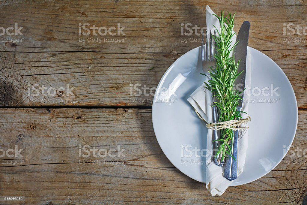 Rustic place setting with rosemary on an old wooden table stock photo