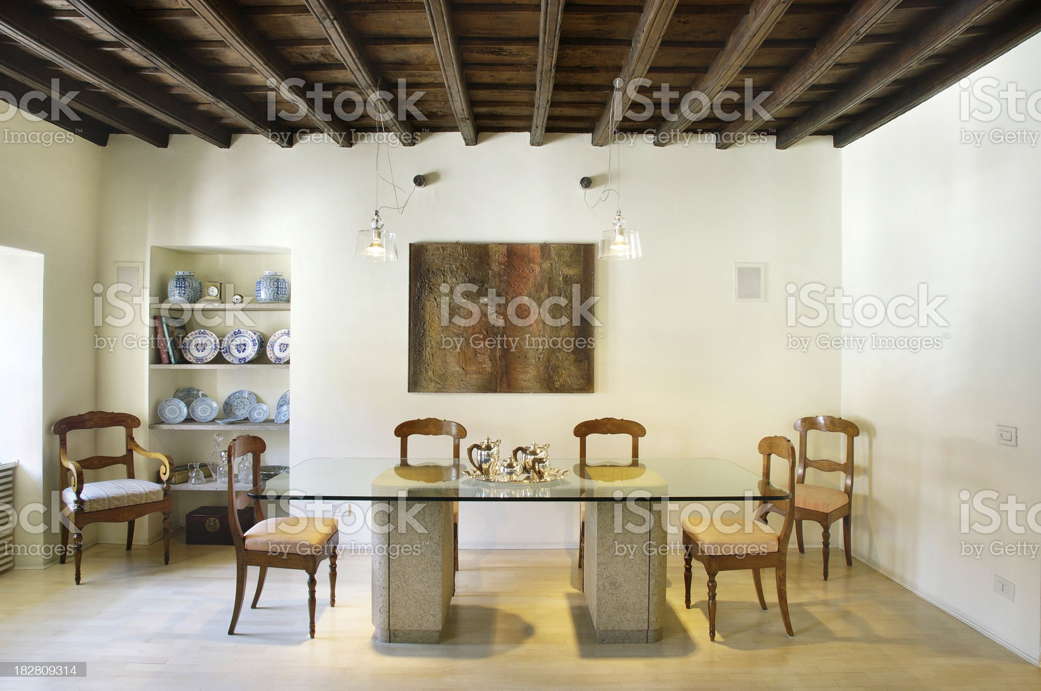Rustic, precious dining room, glass table, wooden chairs, porcelaine royalty-free stock photo
