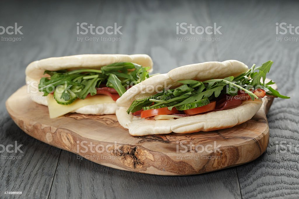 rustic sandwiches with ham arugula and tomatoes in pita bread stock photo