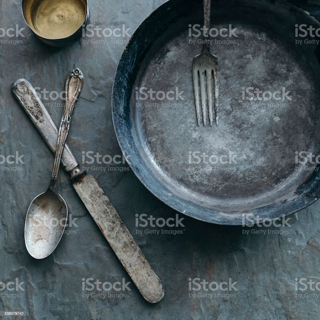 Rustic silverware arranged with skillet and cup stock photo