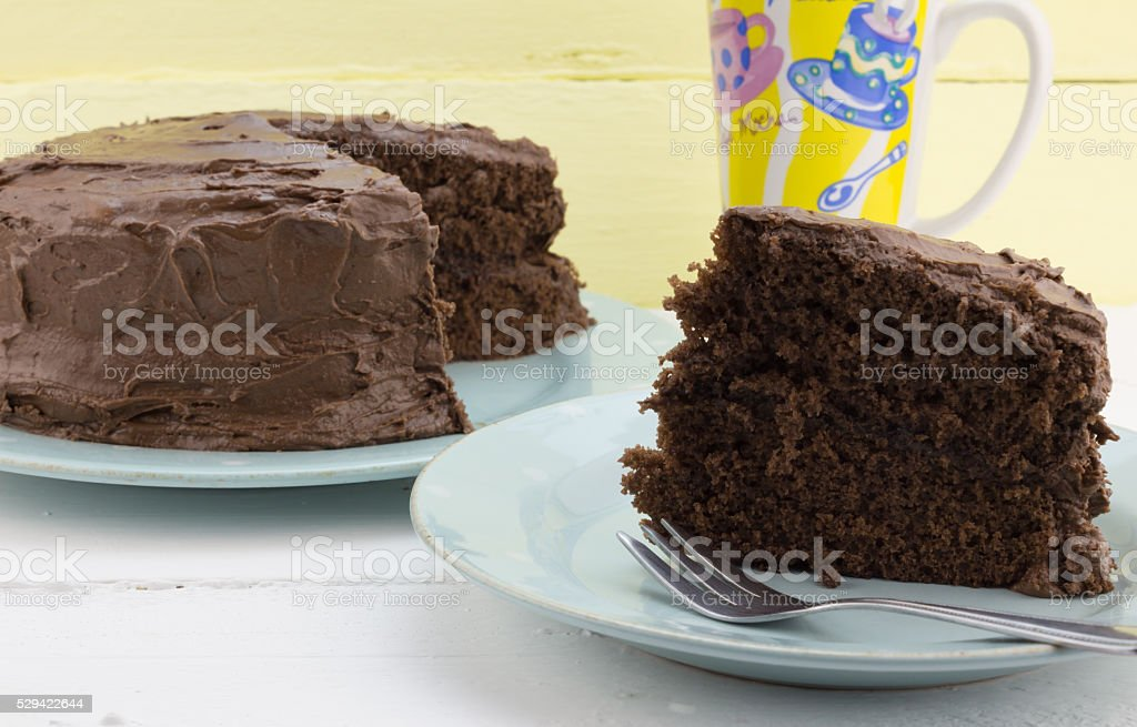 Rustic slice of chocolate cake on blue plate stock photo