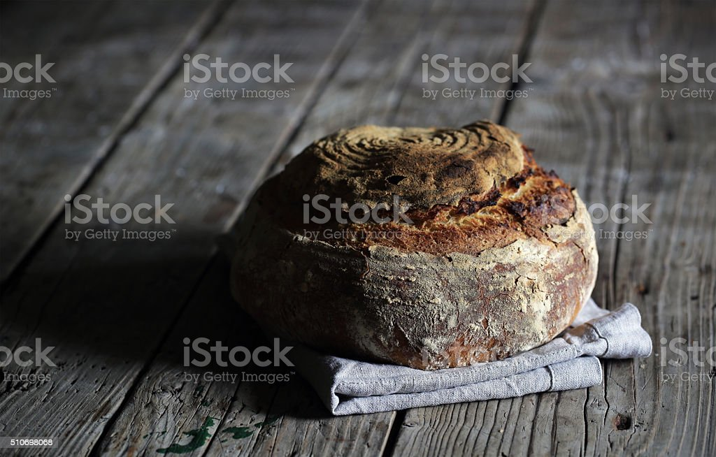 Rustic sourdough loaf, artesan bread on wood stock photo