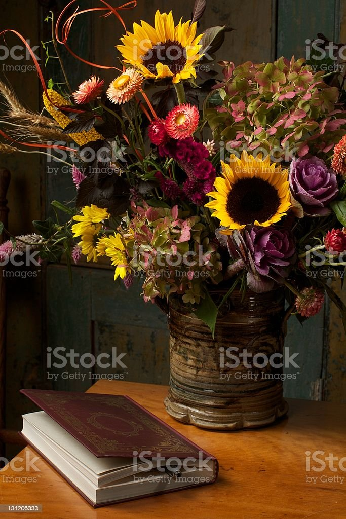 Rustic still life with autumn flowers and leather bound book stock photo