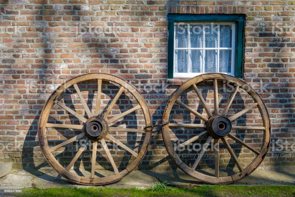 Rustic wagon wheels in front of a bricked wall stock photo