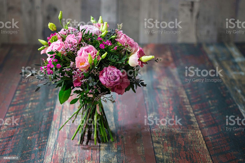 Rustic wedding bouquet with pink roses and Lisianthus flowers. stock photo