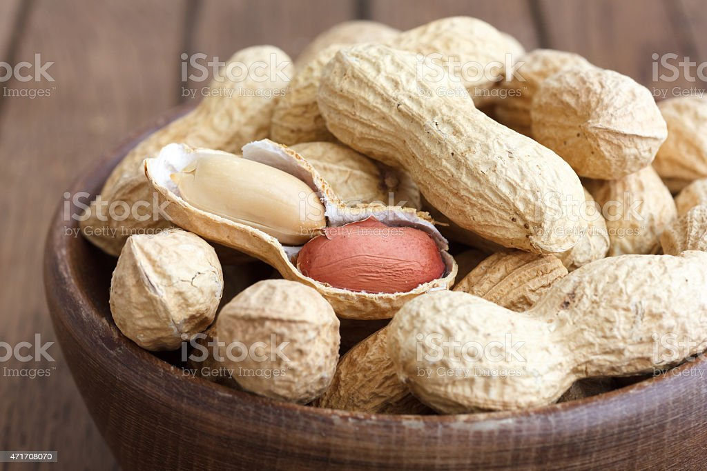 Rustic wood bowl of peanuts in shells. stock photo