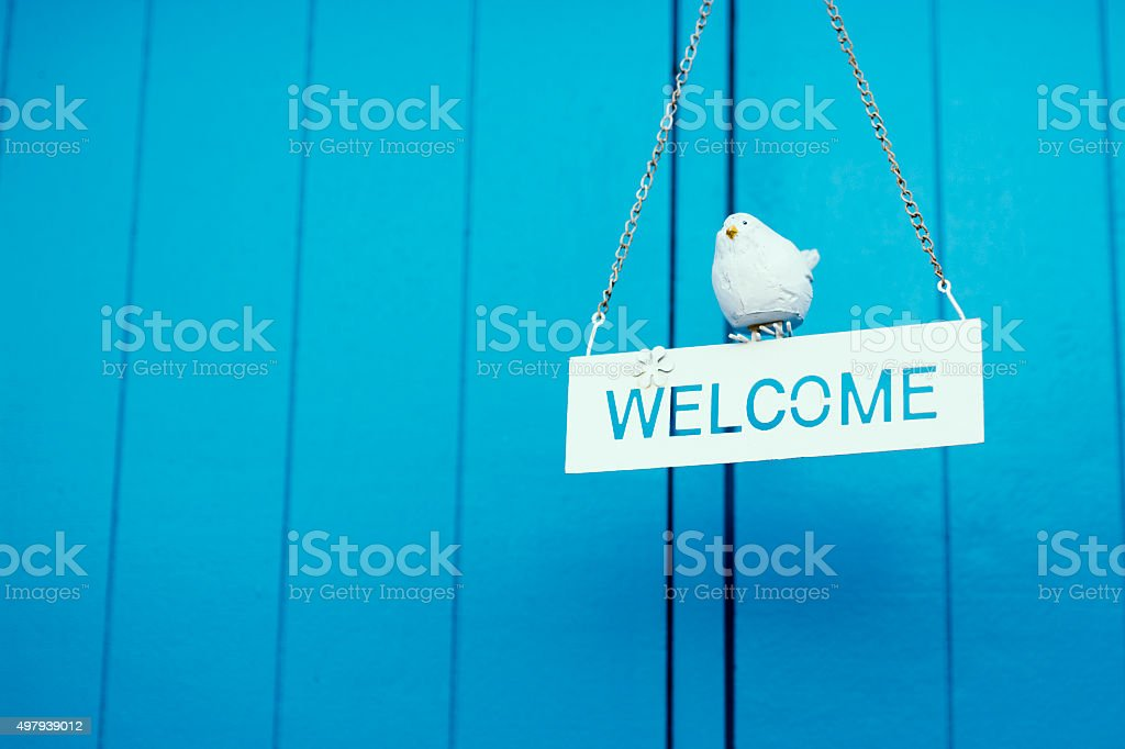 Rustic wood welcome sign hanging on blue background stock photo