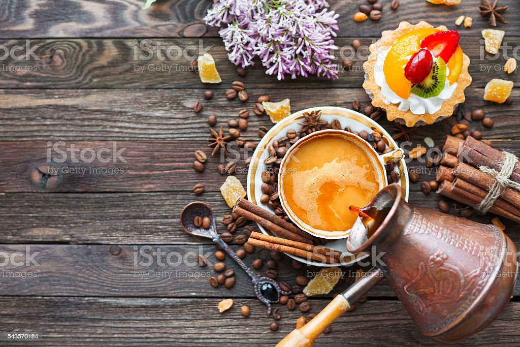 Rustic wooden background with coffee cup, fruit tart, cinnamon stock photo