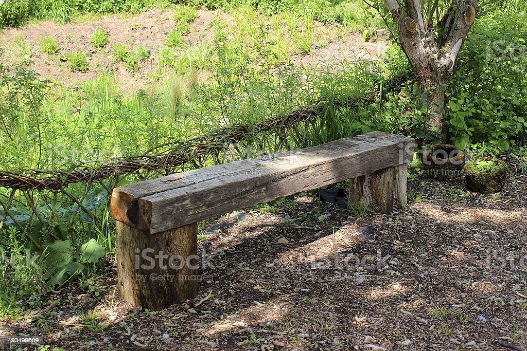 Rustic wooden bench / garden seat with willow weaving hedge image royalty-free stock photo