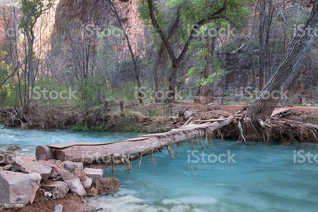 Rustic wooden bridge over a small river stock photo