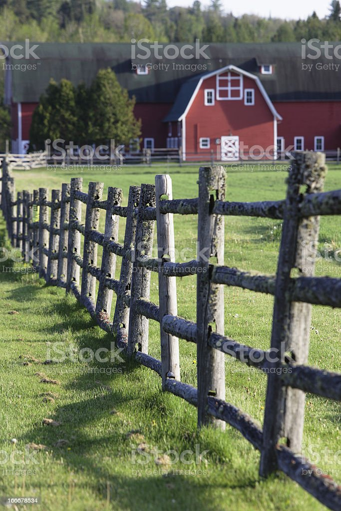 Rustic Wooden Fence and Distant Red Barn stock photo