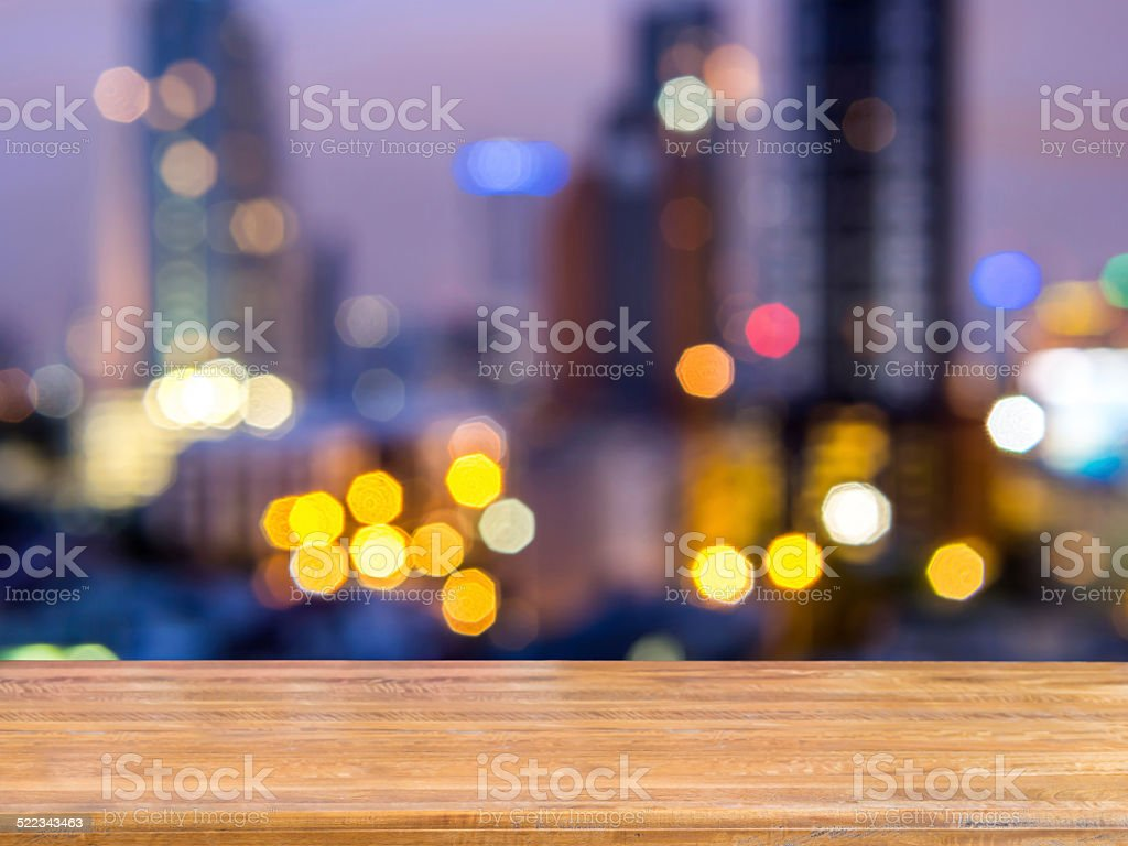 Rustic wooden planks over abstract bokeh cityscape night background stock photo