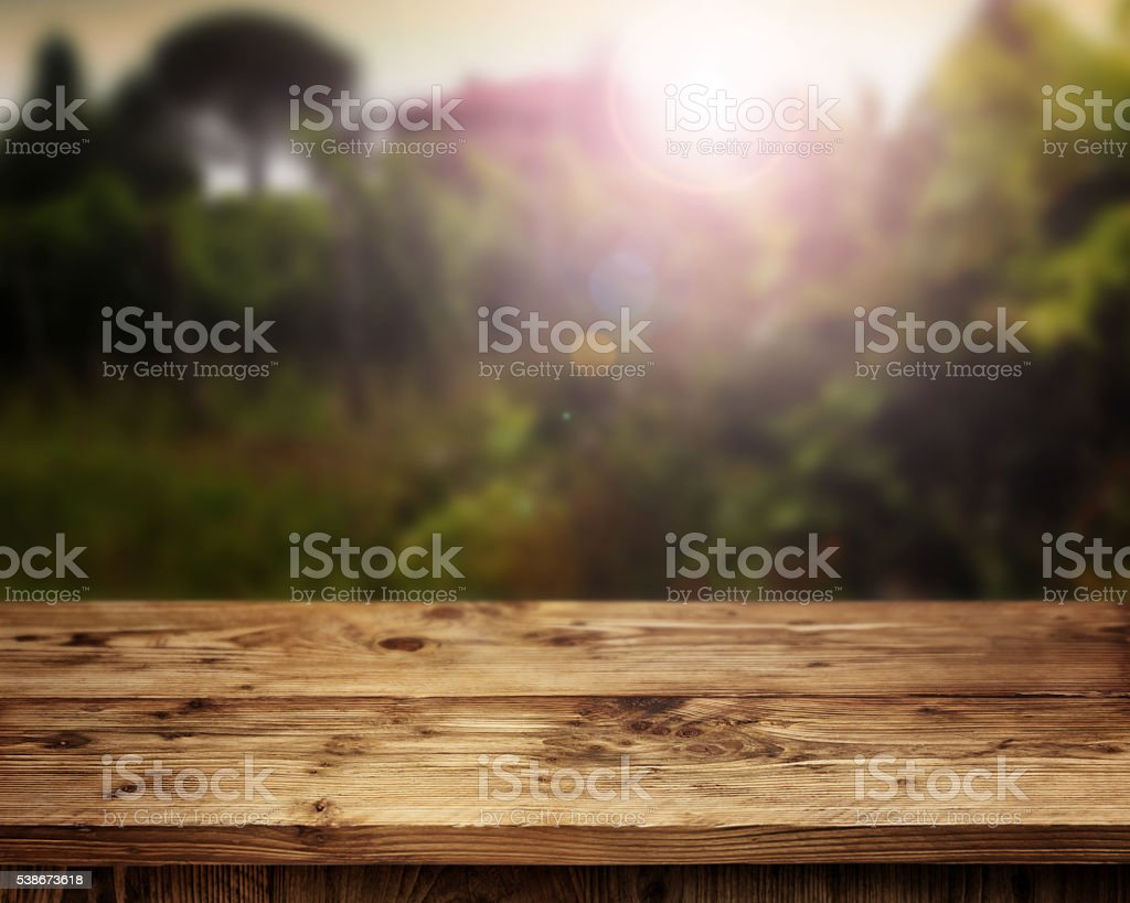 Rustic wooden table in front of a vineyard stock photo