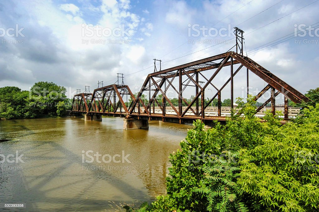 Rusting railroad bridge over the River Raisin at Monroe MI stock photo