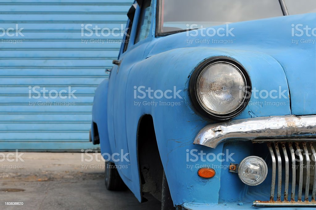 Rusty American oldtimer car in front of blue background stock photo