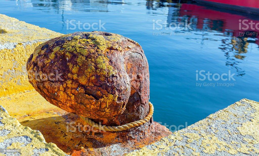 Rusty bitt in harbor stock photo
