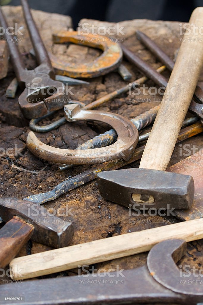 Rusty blacksmith tools and horseshoes royalty-free stock photo