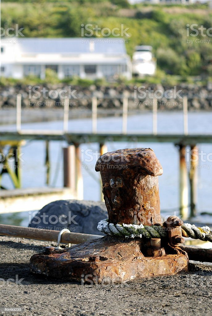 Rusty bollard with rope attached, on New Plymouth wharf stock photo