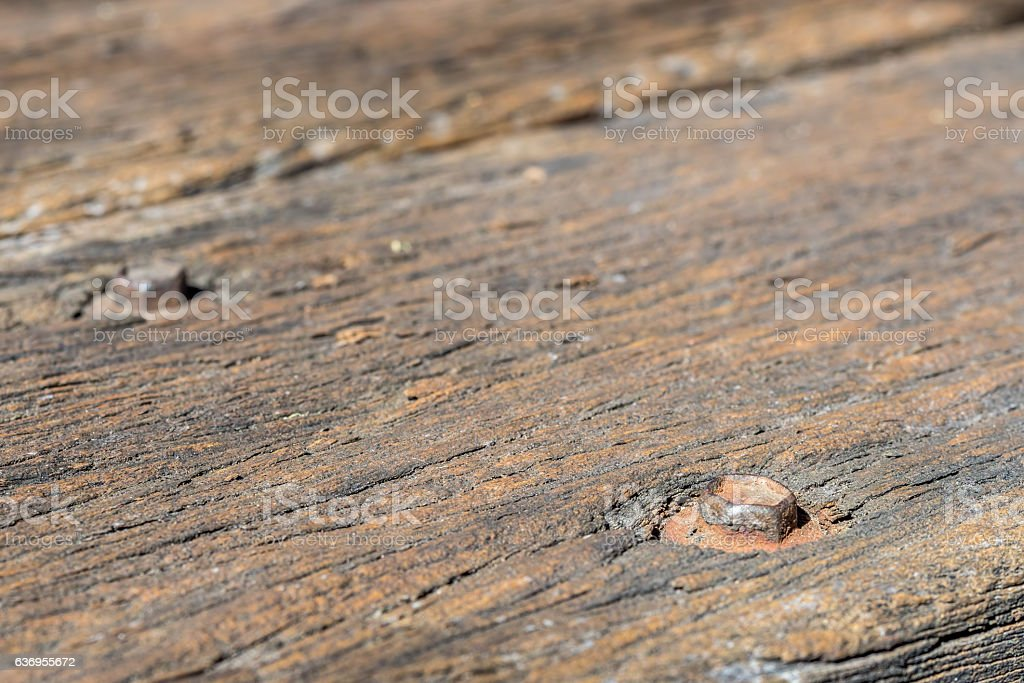 Rusty bolts on a wooden plank stock photo
