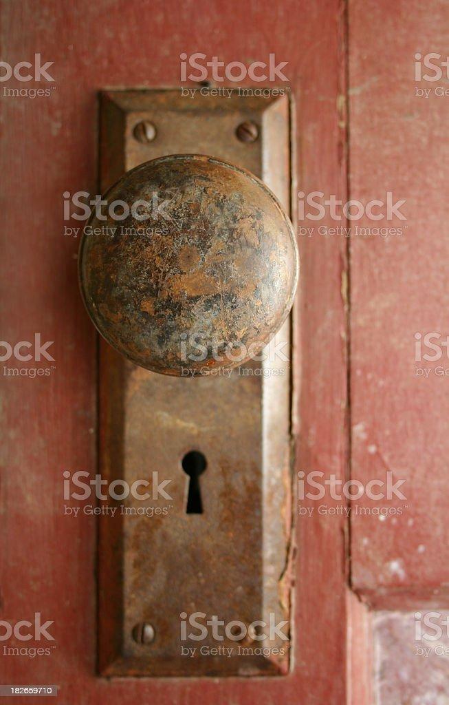 Rusty bronze doorknob on a red door royalty-free stock photo