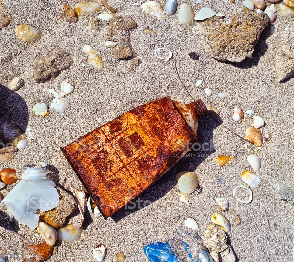 Rusty can in the beach stock photo