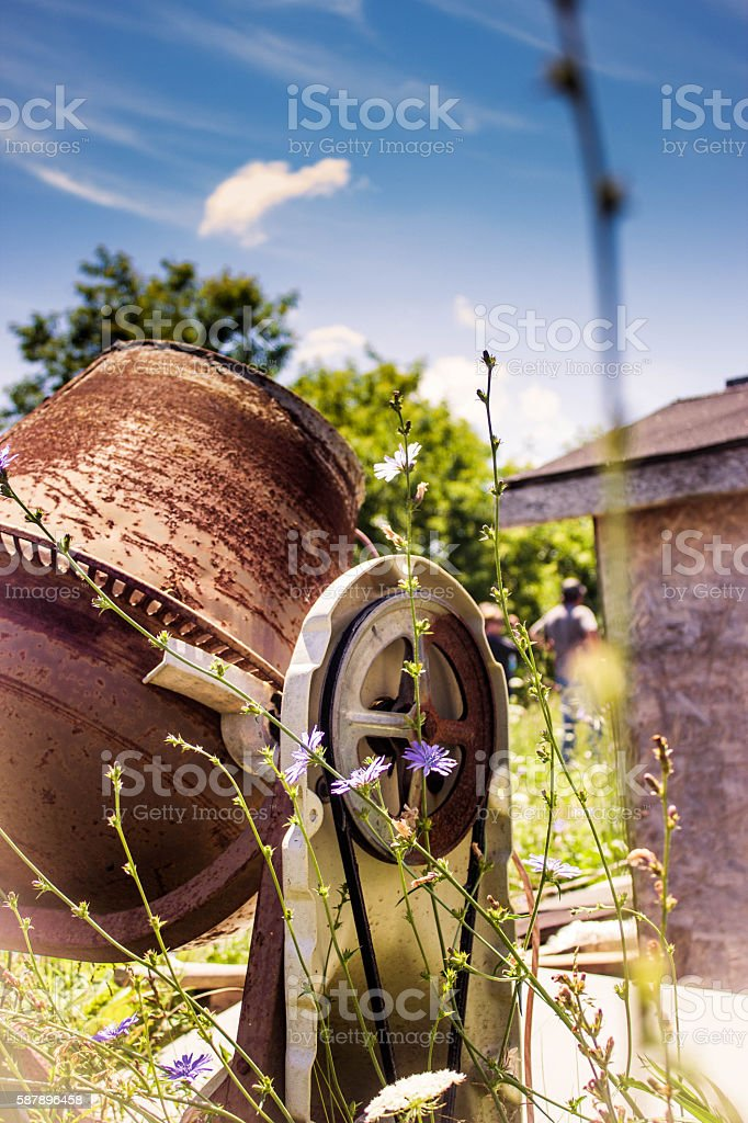 Rusty cement mixer reclaimed by nature stock photo