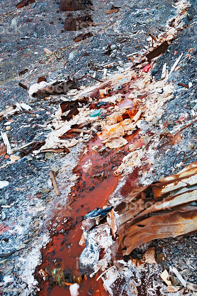 Rusty, dirty stream flowing through the technological waste landfill. stock photo