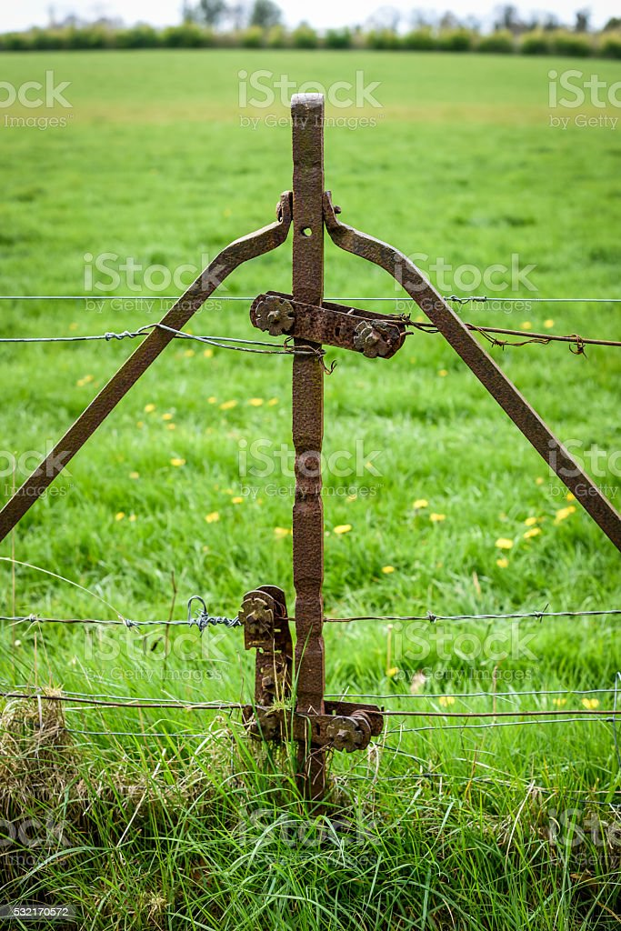 Rusty Fence Post with Tensioner stock photo
