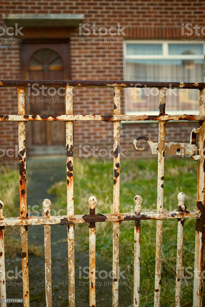 rusty gate at the entrance of a brick house, abandoned stock photo