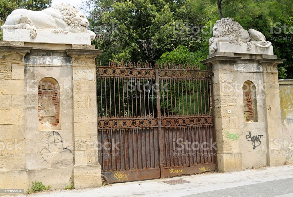 rusty gate with two marble lions royalty-free stock photo
