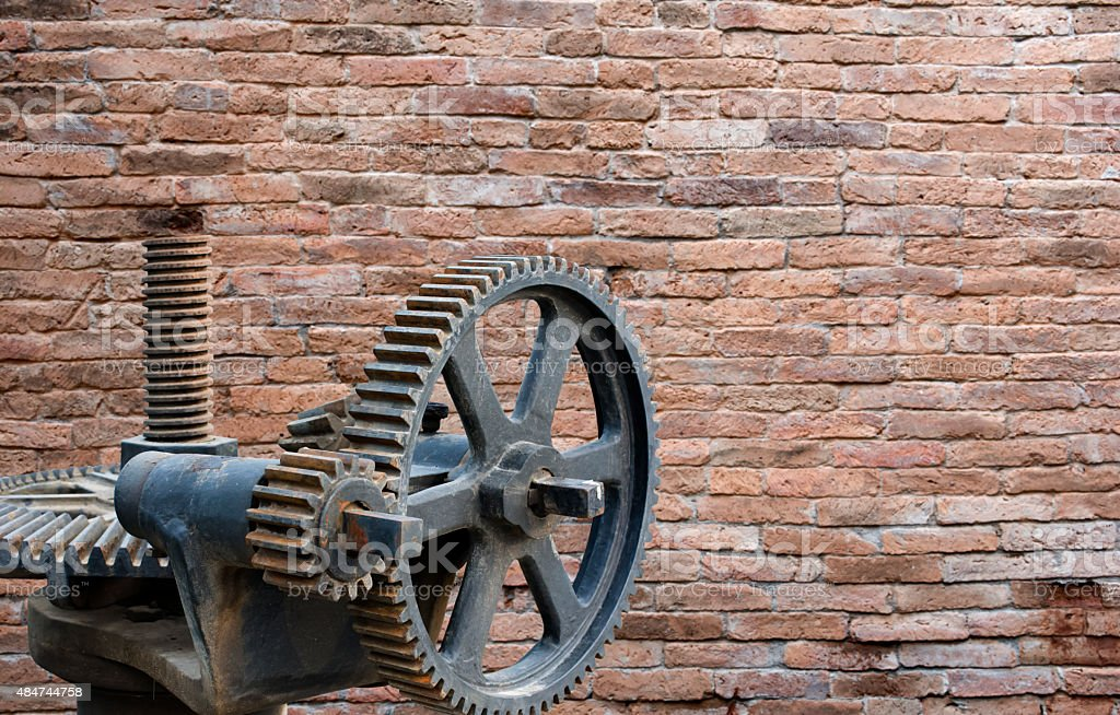 Rusty gears and red brick wall in background royalty-free stock photo