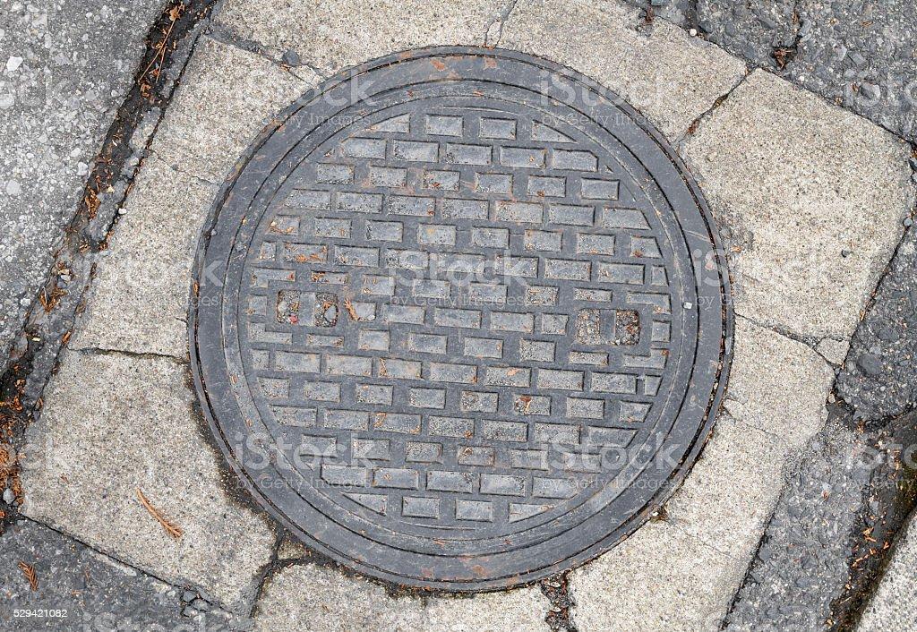 Rusty, grunge manhole cover stock photo