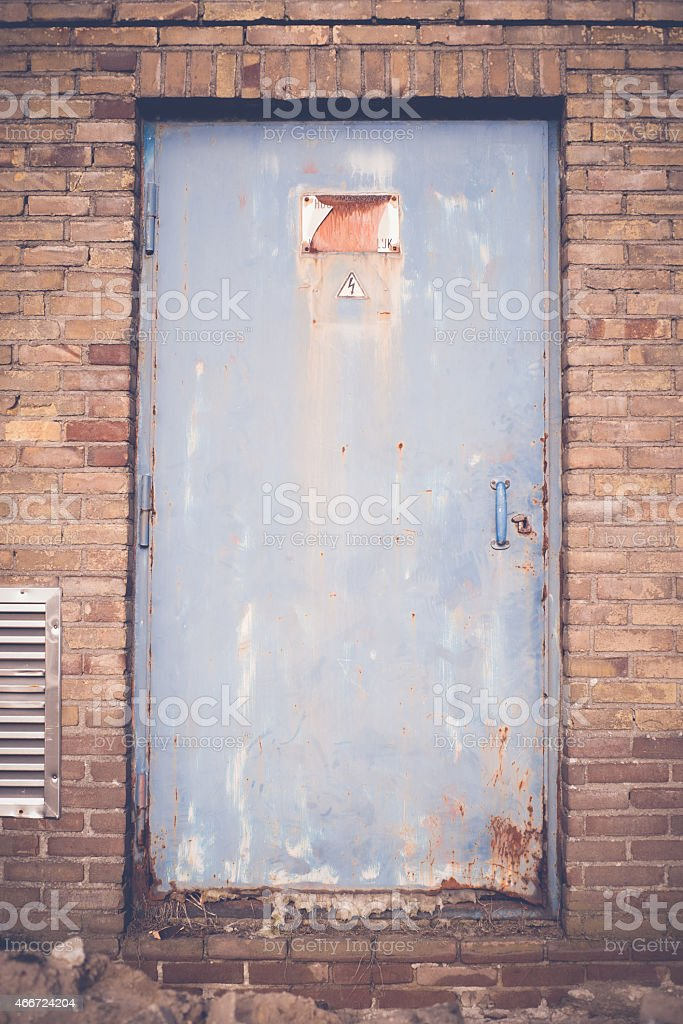 Rusty high voltage warning sign at a old metal door stock photo