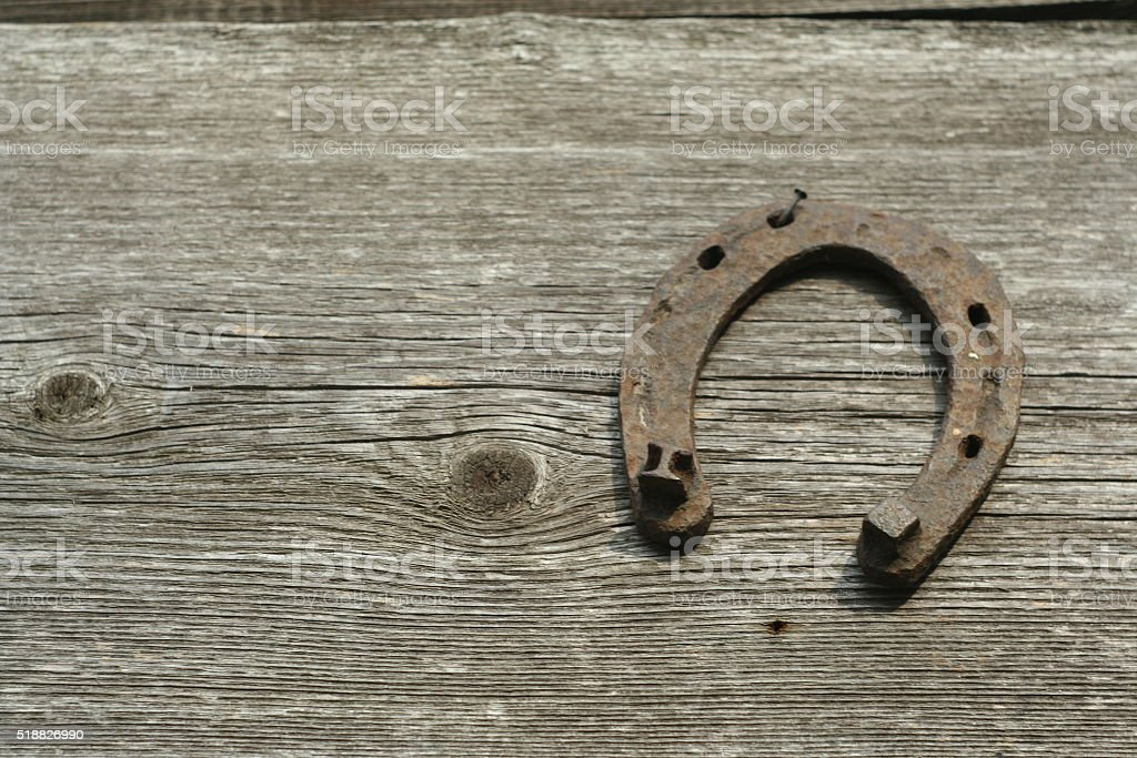 Rusty horseshoes on a wooden background. stock photo