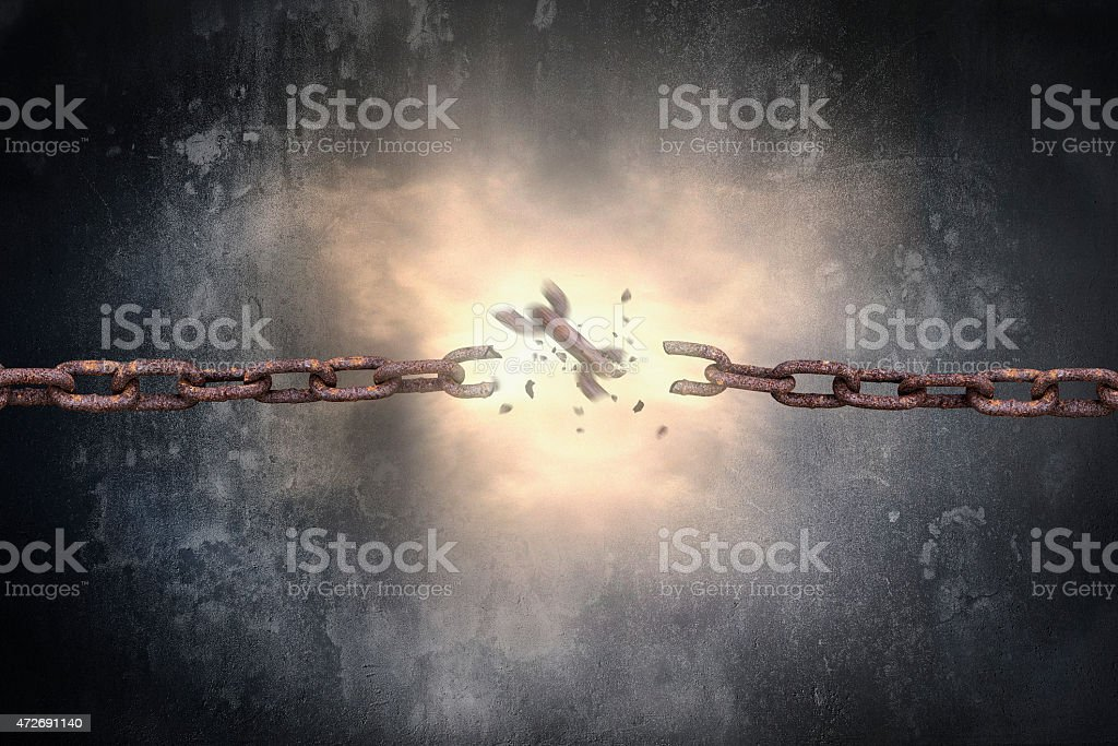Rusty iron chains broken with spark light and dark wall stock photo