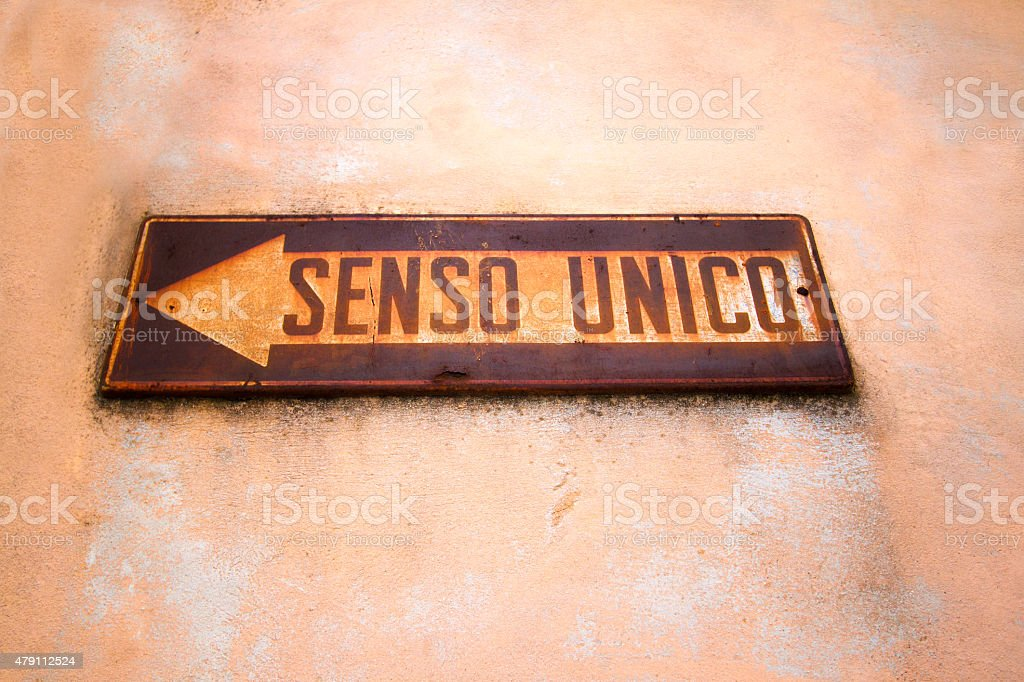 Rusty Italian One-Way Sign ('SENSO UNICO') Against Pink Wall stock photo