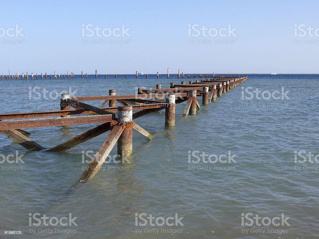 rusty jetty in blue ocean royalty-free stock photo