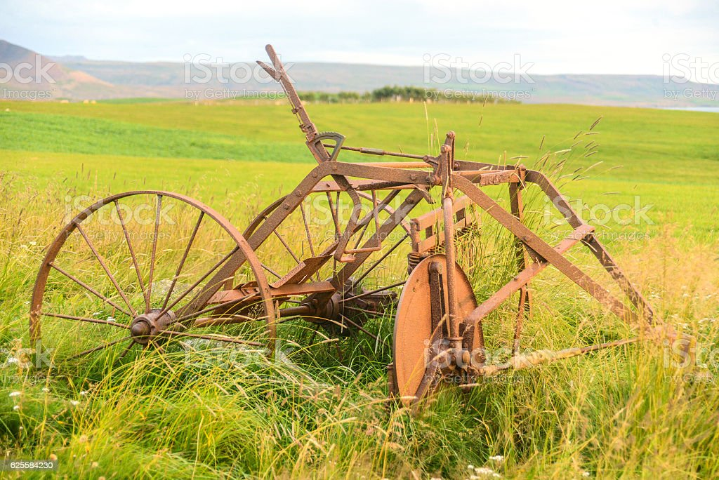rusty land machine on field stock photo
