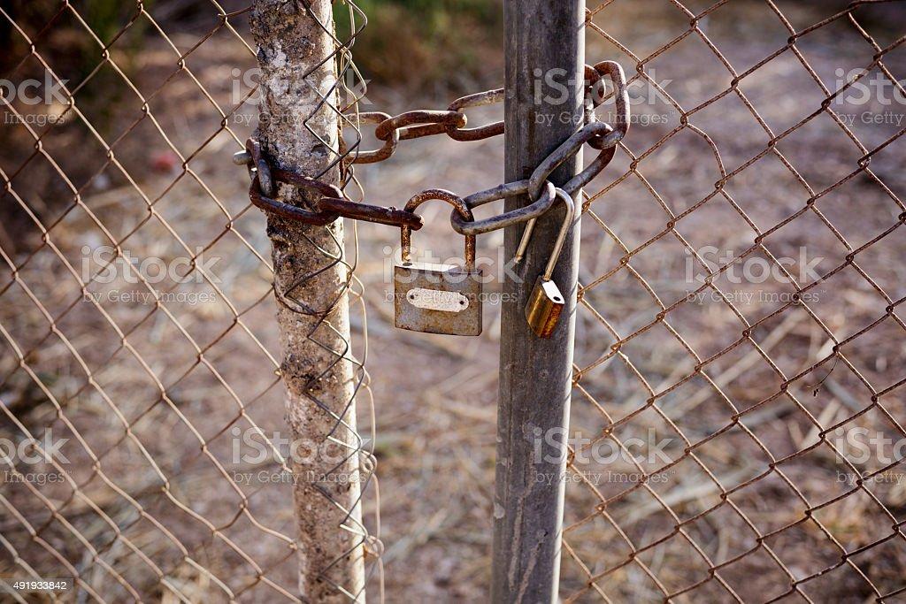 Rusty lock and chain locking the gates stock photo